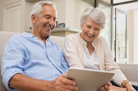 senior-couple-smiling-tablet