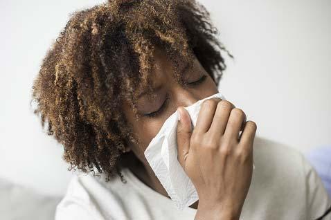 woman-sneezing-into-facial-tissue