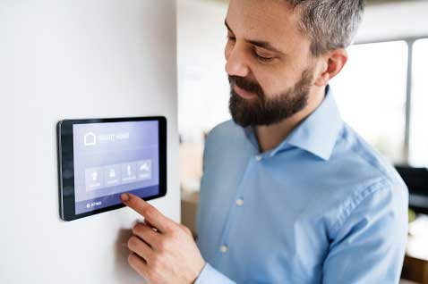 Man-using-smart-thermostat-at-home