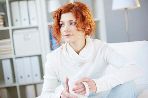 woman-with red-hair-in-white-holding-mug